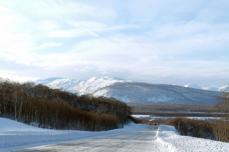 The Road on west Beauty In Nature Cloud - Sky Cold Temperature Day Landscape Mountain Mountain Range Nature Scenics Sky Snow Snowcapped Mountain Tranquility Tree Winter