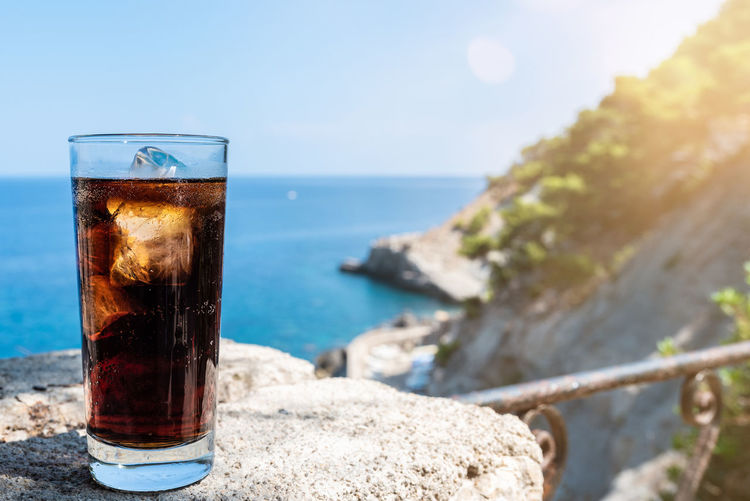 Close-up Cola Day Drink Drinking Glass Focus On Foreground Food And Drink Freshness Glass Horizon Horizon Over Water Ice Cube Nature No People Outdoors Refreshment Sea Sky Sunlight Water