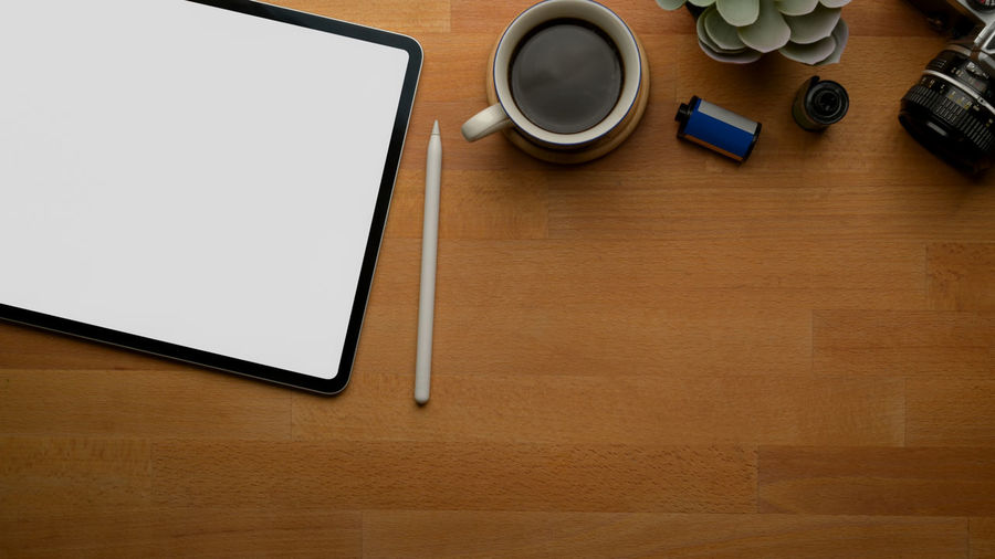 Directly above shot of coffee cup with digital tablet on table
