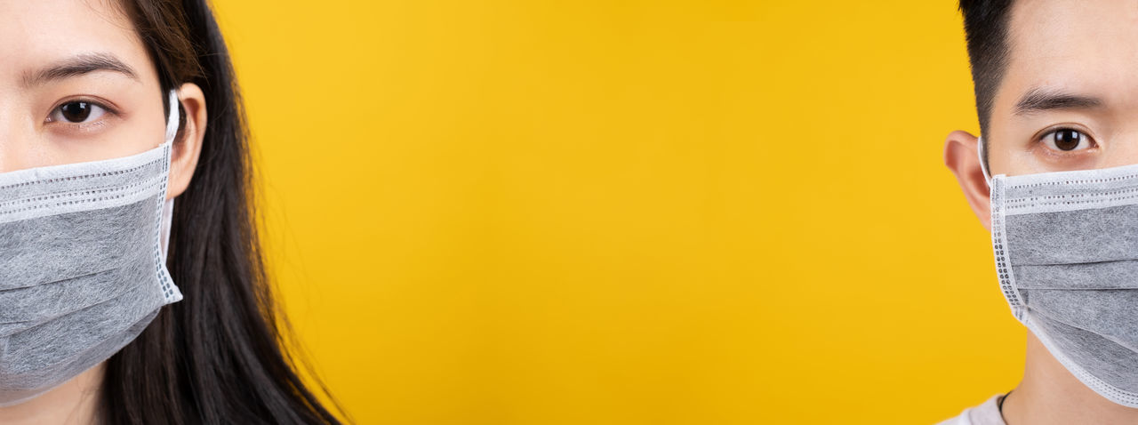 Close-up portrait of a beautiful young woman over yellow background