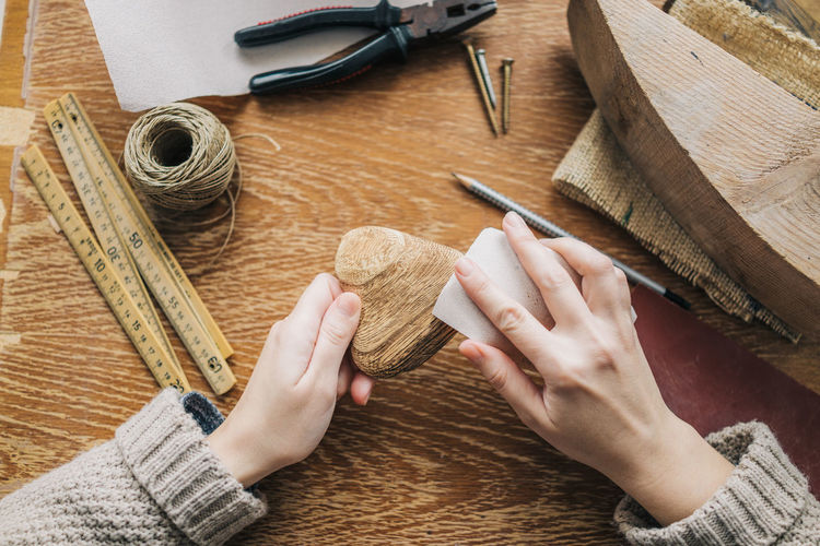 Cropped hands of woman carving wood at table