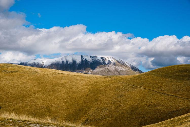 Scenic view of landscape against sky in castelluccio, umbria italy