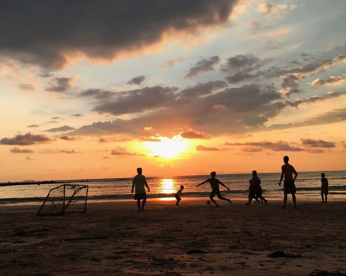 Silhouette males friends playing soccer at beach during sunset