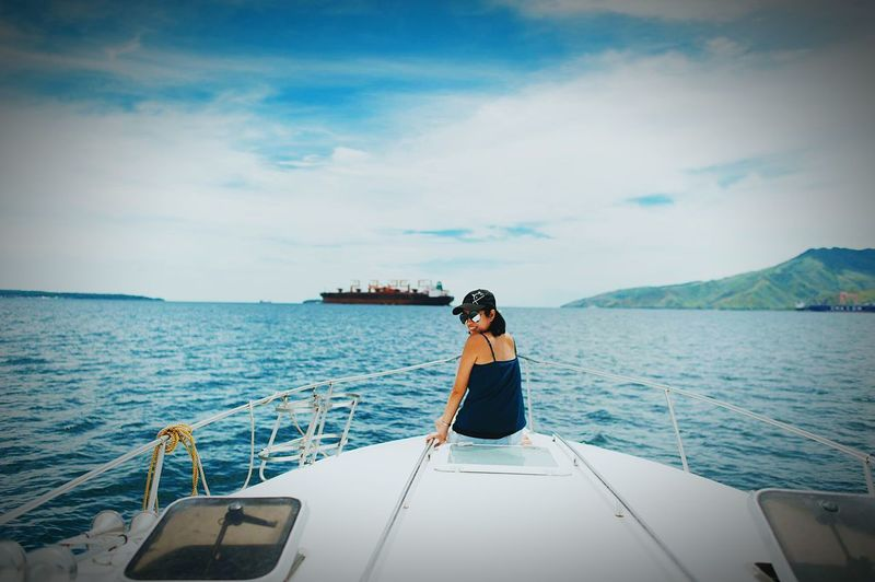 Woman Sitting In Boat On Sea Against Sky