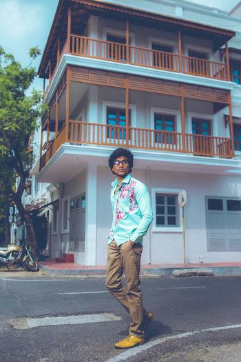Full length of boy standing on street against building