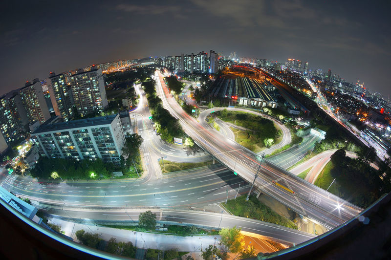 High angle view of light trails on highways in city at night