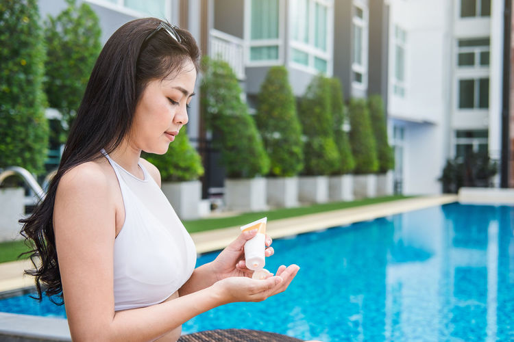 Woman applying lotion while sitting at poolside