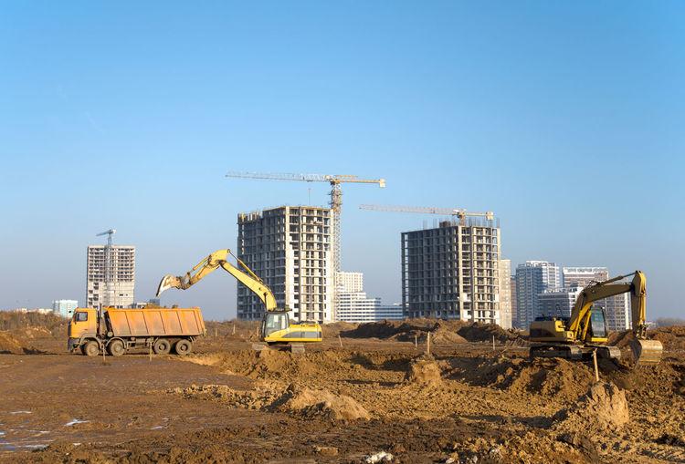 Crane at construction site against clear blue sky