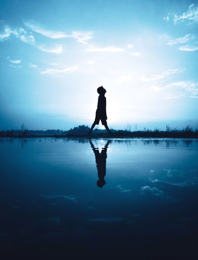 Silhouette boy reflecting on calm lake against sky during sunset