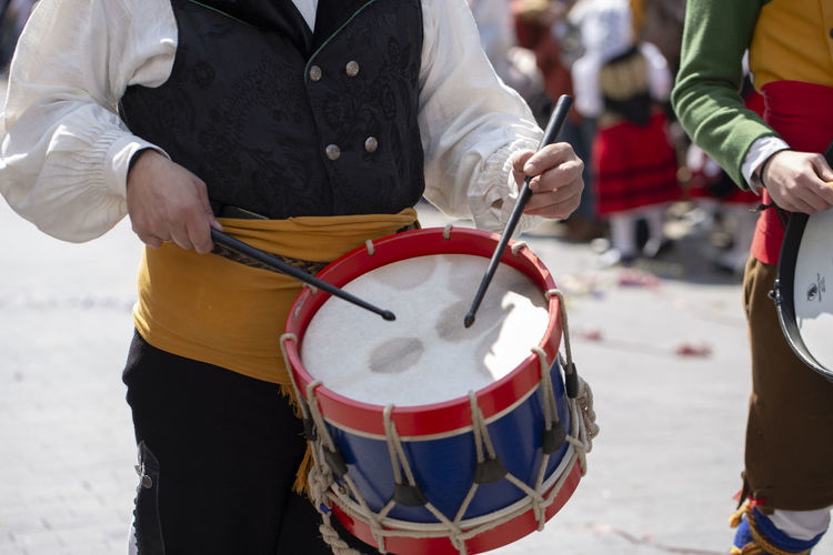 Midsection of men playing drums on street