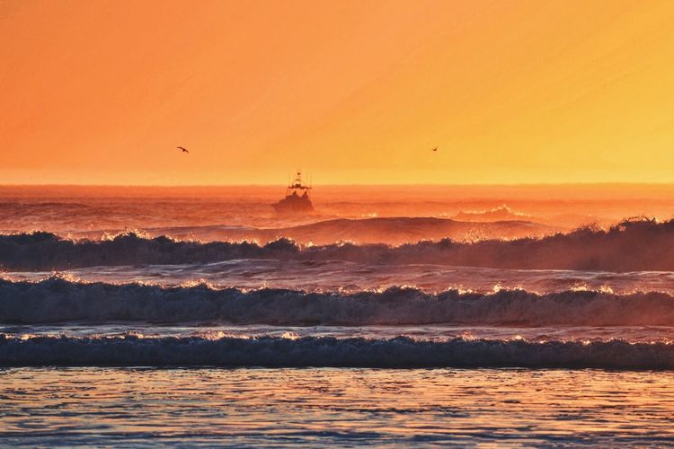 Waves In Sea Against Orange Sky During Sunset