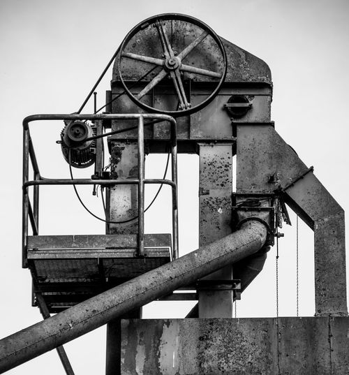 Low angle view of old machinery against sky