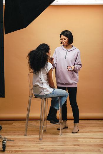 Full length of artist applying make-up on woman face in studio