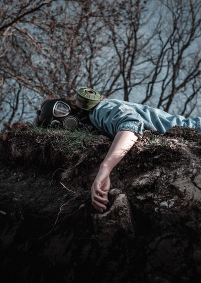 Low angle portrait of woman wearing gas mask while lying on land