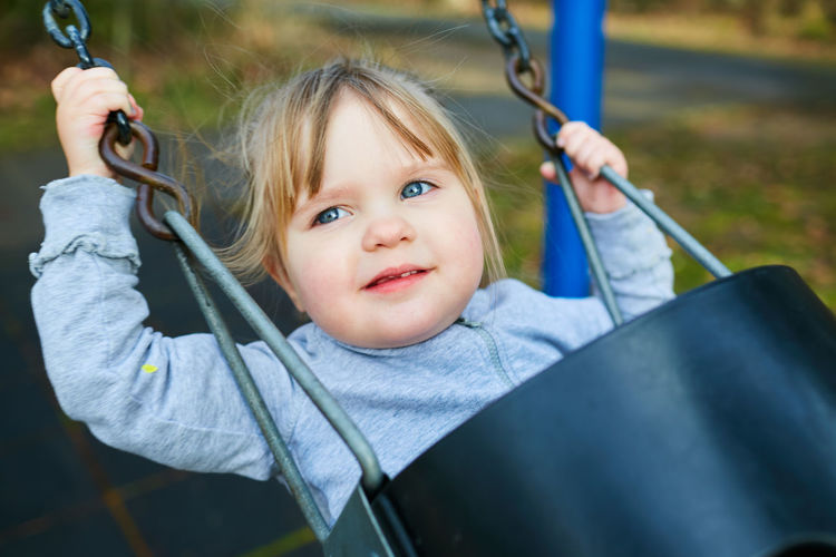 Portrait of a smiling girl on swing in playground