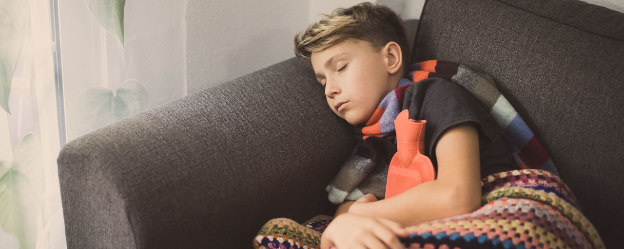 High angle view of ill boy lying on sofa at home