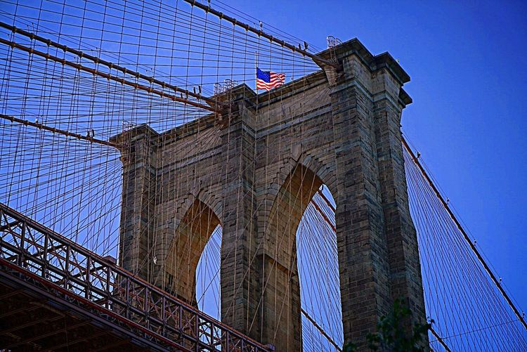 Brooklyn Bridge, New York City. Architecture Built Structure Flag Sky City Patriotism Low Angle View No People Travel Destinations Building Exterior Outdoors Connection Bridge - Man Made Structure Day Suspension Bridge Brooklyn Bridge / New York NYC NYC Skyline New York City