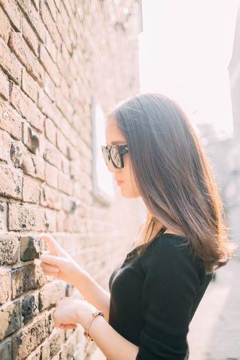 Side view of young woman standing by wall