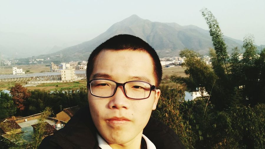 Close-up of young man in eyeglasses standing against mountain