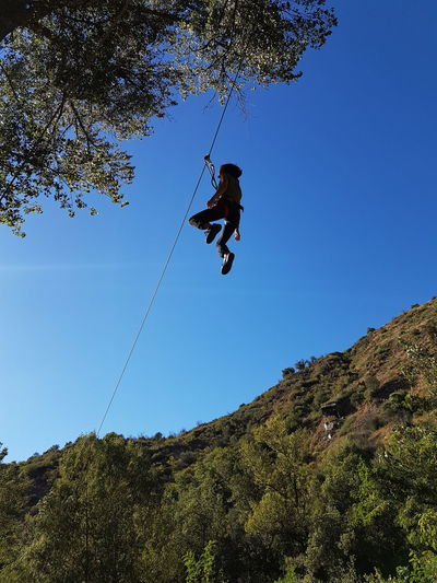 Low Angle View Of Person Hanging On Zip Line Against Clear Blue Sky