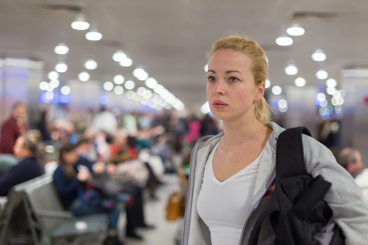 Beautiful woman looking away while standing at airport