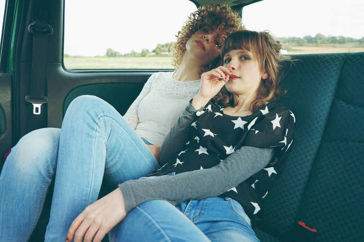 Female friends sitting in car