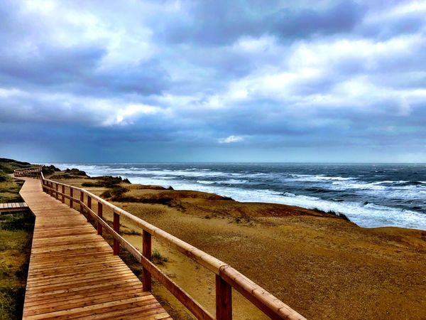 Sky Sea Water Cloud - Sky Land Beach Horizon Over Water Beauty In Nature Horizon Scenics - Nature Tranquility Tranquil Scene Nature No People Day Railing Sand Outdoors Direction