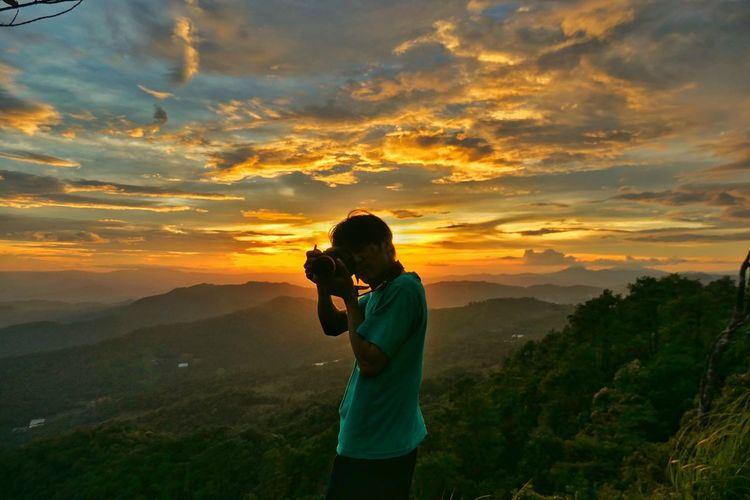 Full length of man photographing at sunset