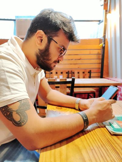 Young man using mobile phone on table