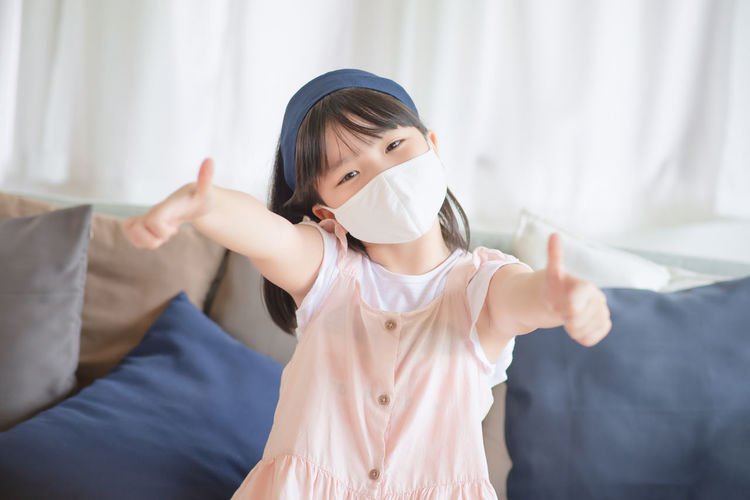 Portrait of girl wearing mask gesturing while sitting on sofa