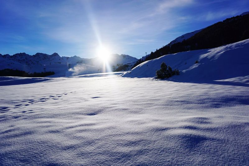 Snowfield against sun Winter Snow Cold Temperature Sky Mountain Beauty In Nature Tranquility Tranquil Scene Scenics - Nature Nature Environment Sunbeam Mountain Range Sunlight Cloud - Sky Landscape No People Frozen Sun Lens Flare