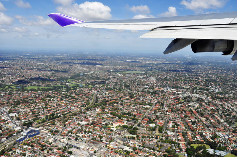 Cropped Image Of Airplane Wing Over Cityscape