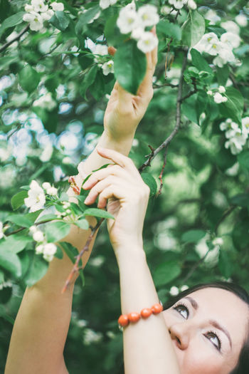 Close-up of woman with hand on plant