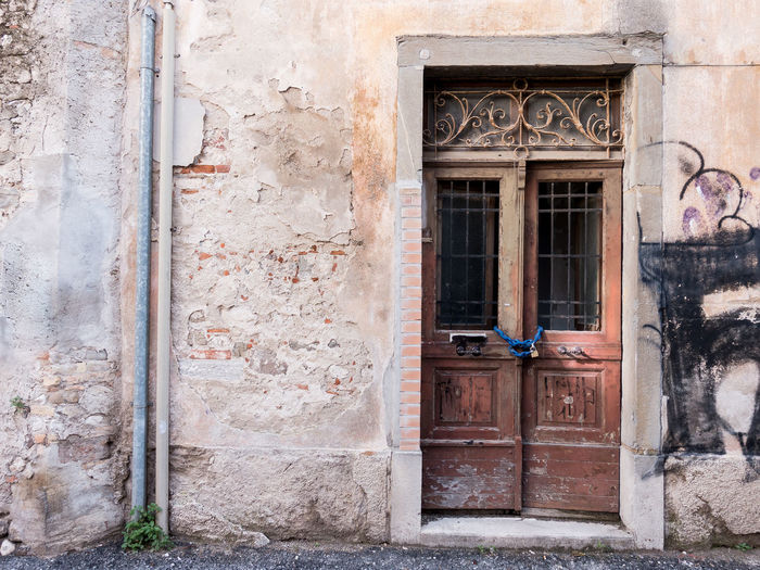 Old closed wooden door with chain and padlock. Architecture Building Exterior Built Structure Window Building Entrance Door Day No People Old Wall - Building Feature House Closed Weathered Residential District Outdoors Security Wall Protection Safety
