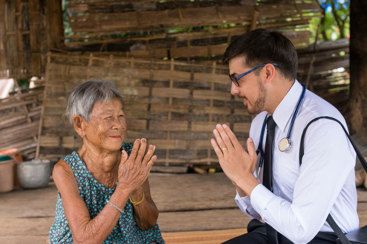 Doctor With Hands Clasped Greeting Senior Woman At Village