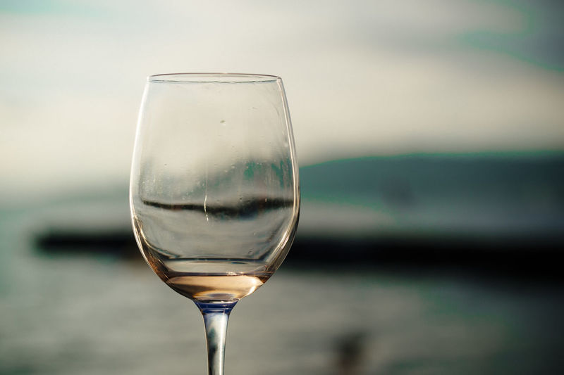 Close-up of wineglass against sky