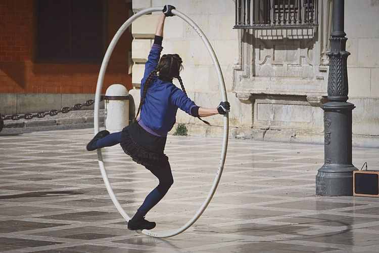Rear View Of Woman Performing Acrobat With Large Ring On Street