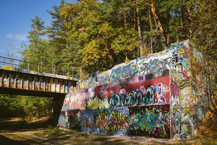 Graffiti on bridge by trees
