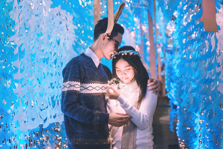 Young Man With Girlfriend Holding Illuminated Lights
