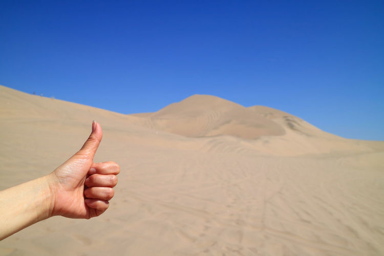 Cropped hand showing thumbs up at desert against sky