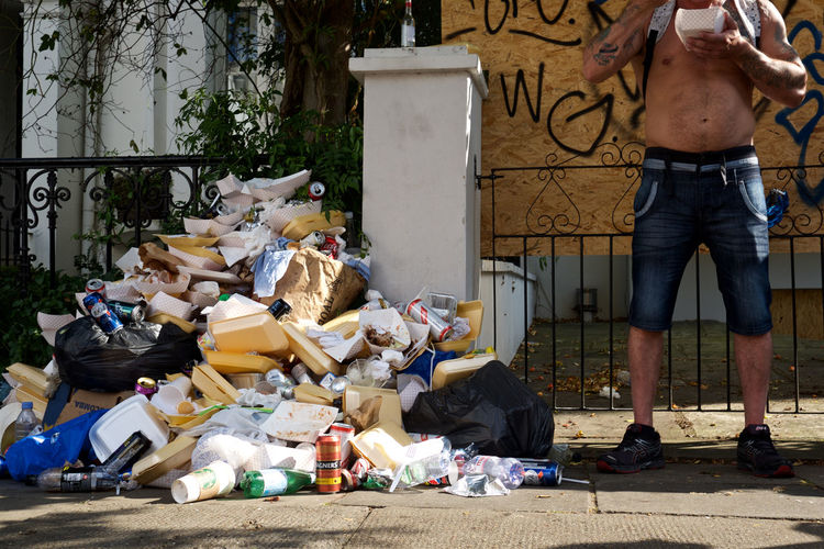 Low section of man standing by garbage on footpath