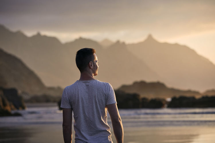 Rear view of pensive man on beach aganinst cliff at golden sunset. beautiful nature in tenerife.