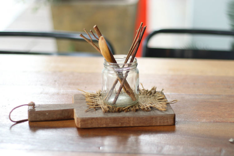 Close-Up Of Sticks In Glass Jar On Cutting Board Over Table