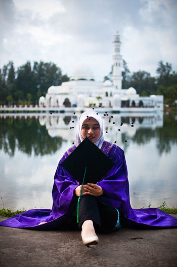Portrait of woman holding mortarboard while sitting against lake with mosque in background
