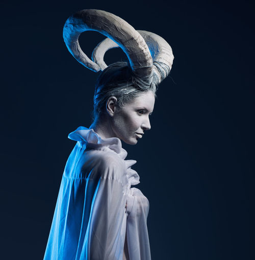 Young woman with horns looking away against black background