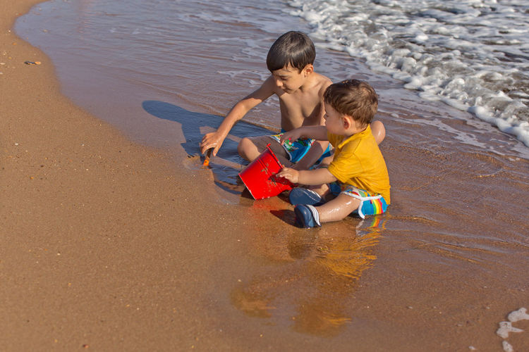 Siblings playing with sand bucket and shovel at the beach 17 Month Old 6 Years Old Arm Outstreched Beach Beachwear Bonding Boys Carefree Caucasian Ethnicity Childhood Day Digging Fun Leisure Activity Lifestyles Outdoors People Real People Sand & Sea Shirtless Siblings Summer Toddler  Togetherness Water