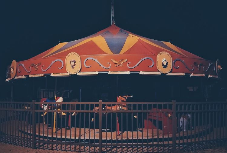 Low angle view of illuminated carousel against sky at night