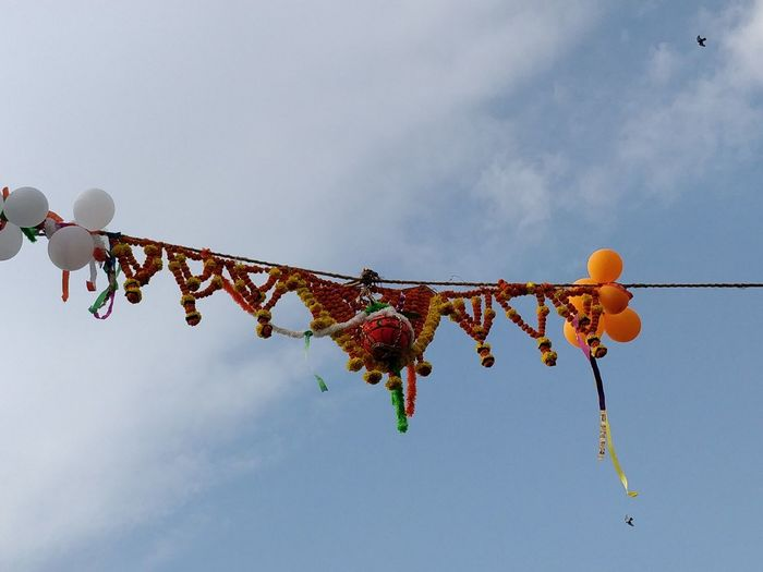 Low angle view of dahi handi decorations against sky
