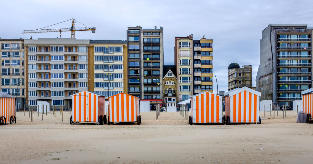Row of colorful beach cabins against buildings in de panne, belgium