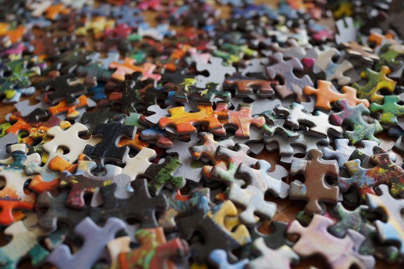 High angle view of multi colored puzzle pieces on table